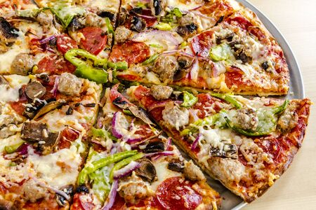 Close up of sliced thin crust supreme pizza sitting on metal pizza pan with fresh meats and vegetables