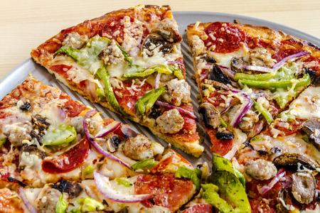 carnes y verduras: Primer plano de rodajas finas corteza de pizza suprema sentado en bandeja para pizza de metal con carnes y verduras frescas