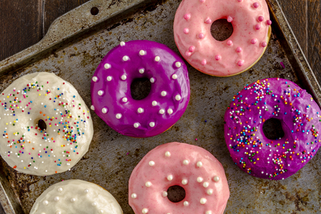Close up of assortment of homemade vanilla bean donuts with colorful icing sitting on metal baking pan photo