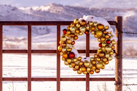 Gold and brown Christmas ornament wreath covered with freshly fallen snow sitting on entrance to mountain ranch fence photo