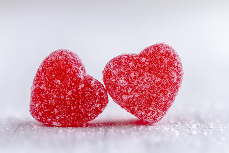 Two cinnamon heart candies coated with sugar sitting on white background
