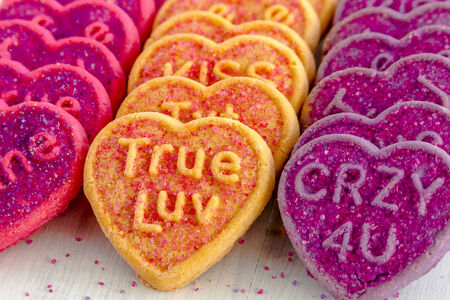 kiss biscuits: Rows of conversation heart cookies in pink, orange and purple with various text messages and sugar sprinkles