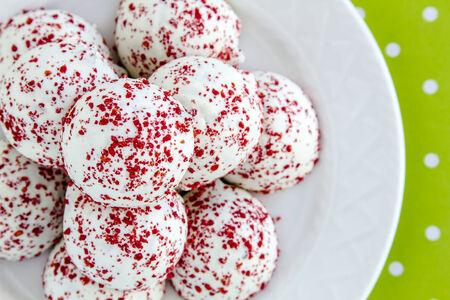 cake balls: Red velvet cake balls covered with white chocolate and red sprinkles on green polka dot background