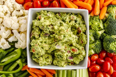 chunky: Bowl of homemade chunky guacamole surrounded by fresh vegetables