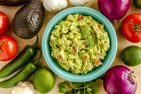 chunky: Homemade chunky guacamole in bright blue bowl garnished with cilantro surrounded by dip ingredients Stock Photo