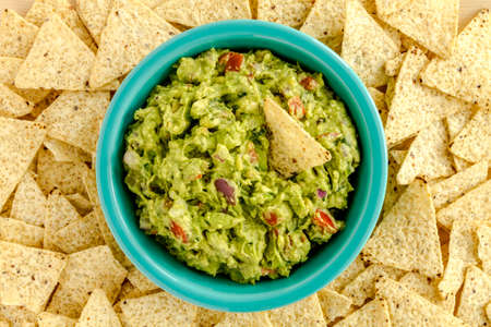 chunky: Homemade chunky guacamole in bright blue bowl surrounded by white corn tortilla chips Stock Photo