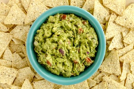tortilla de maiz: Guacamole hecho en casa en un taz�n azul brillante rodeado de chips de tortilla de ma�z blanco