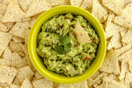 tortilla de maiz: Guacamole hecho en casa en un taz�n verde brillante rodeado de chips de tortilla de ma�z blanco