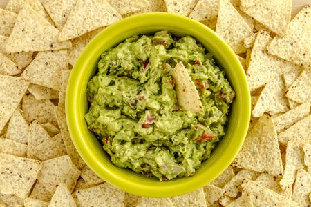 chunky: Homemade chunky guacamole in bright green bowl surrounded by white corn tortilla chips Stock Photo
