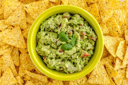 tortilla de maiz: Guacamole hecho en casa en un taz�n verde brillante rodeado de chips de tortilla de ma�z amarillo
