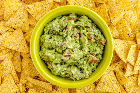 chunky: Homemade chunky guacamole in bright green bowl surrounded by yellow corn tortilla chips
