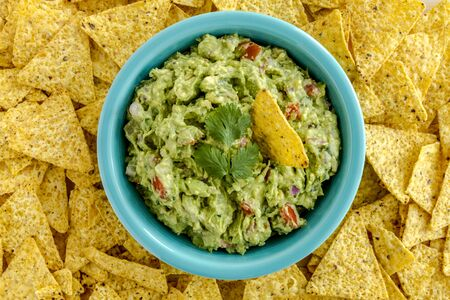chunky: Homemade chunky guacamole in bright blue bowl surrounded by yellow corn tortilla chips Stock Photo