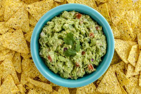 tortilla de maiz: Guacamole hecho en casa en un taz�n azul brillante rodeado de chips de tortilla de ma�z amarillo