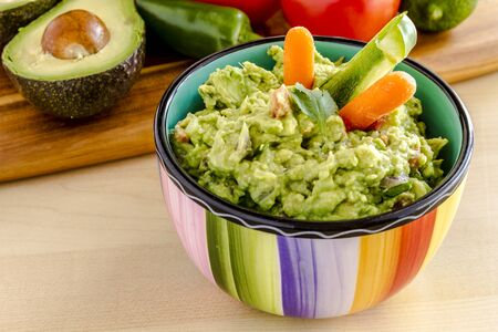 chunky: Fresh chunky guacamole in colorful bowl garnished with raw carrots and green peppers and cilantro