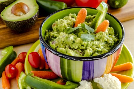 chunky: Fresh chunky guacamole in colorful bowl sitting on bright green plate garnished with raw carrots and green peppers and cilantro surrounded by raw vegetables