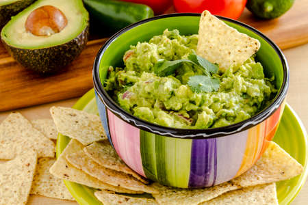 chunky: Fresh chunky guacamole in colorful bowl garnished with white corn tortilla chip and cilantro Stock Photo