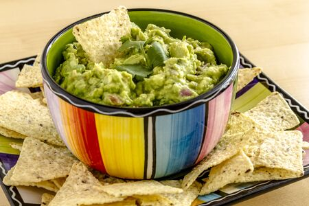 chunky: Homemade chunky guacamole in colorful bowl garnished with white corn tortilla chip and cilantro