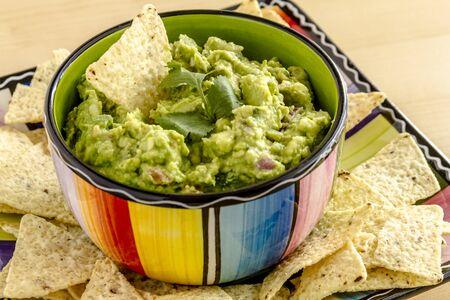 tortilla de maiz: Guacamole hecho en casa en un taz�n colorido adornado con blanco chip de tortilla de ma�z y cilantro Foto de archivo