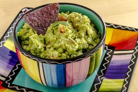 tortilla de maiz: Guacamole hecho en casa en un taz�n colorido adornado con azul de chips de tortilla de ma�z y cilantro Foto de archivo