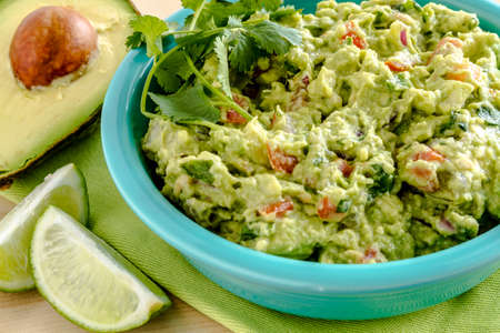chunky: Close up of homemade chunky guacamole in bright blue bowl sitting on green napkin with lime wedges and avocado half