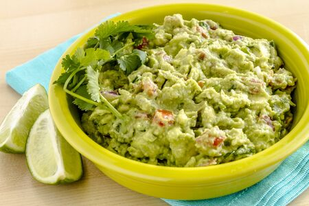 chunky: Close up of homemade chunky guacamole in bright green bowl sitting on blue napkin with lime wedges