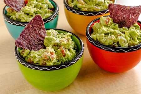 chunky: Homemade chunky guacamole in four colorful individual serving bowls garnished with blue corn tortilla chip