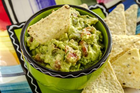 tortilla de maiz: Close up de guacamole hecho en casa en un taz�n verde brillante que se sienta en el plato de colorido con chips de tortilla de ma�z blanco