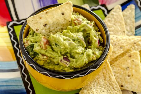 chunky: Close up of homemade chunky guacamole in bright yellow bowl sitting on colorful plate with white corn tortilla chips