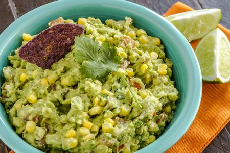 chunky: Close up of homemade chunky guacamole with fresh corn in bright blue bowl and lime wedges sitting on orange napkin Stock Photo