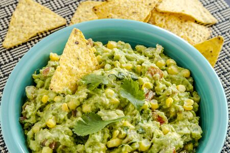 chunky: Close up of homemade chunky guacamole with fresh corn in bright blue bowl and yellow corn tortilla chips