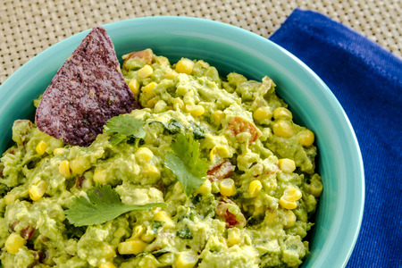 chunky: Close up of homemade chunky guacamole with fresh corn in bright blue bowl sitting on dark blue napkin