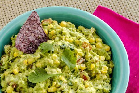 chunky: Close up of homemade chunky guacamole with fresh corn in bright blue bowl sitting on pink napkin