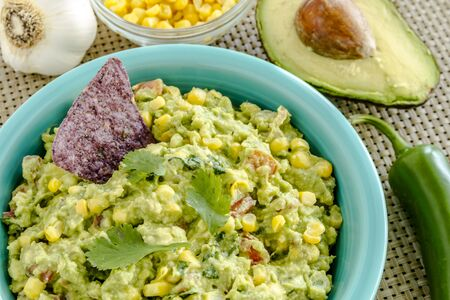 tex mex: Close up of homemade chunky guacamole with fresh corn in bright blue bowl surrounded by fresh ingredients Stock Photo