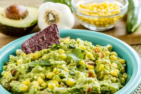 chunky: Close up of homemade chunky guacamole with fresh corn in bright blue bowl surrounded by fresh ingredients Stock Photo