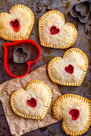 cookie cutters: Heart shaped cherry hand pies sitting on metal baking pan with heart cookie cutters