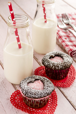 doilies: Two chocolate cupcakes with heart shaped cutouts filled with pink frosting sitting on red lace doilies and two bottles of milk with straws