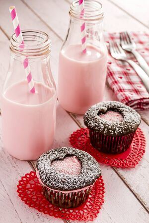 doilies: Two chocolate cupcakes with heart shaped cutouts filled with pink frosting sitting on red lace doilies and two bottles of strawberry milk with straws