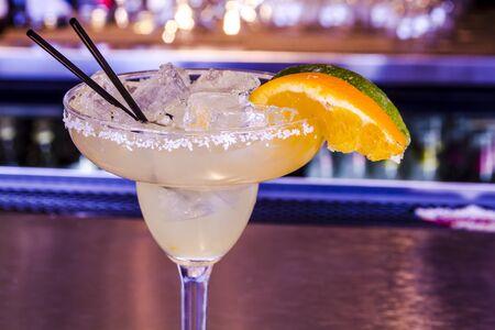 coctel margarita: Primer plano de margarita fresca de lim�n con cubitos de hielo en vaso de margarita que se sientan en la barra superior con guarnici�n de naranja y lim�n cu�as