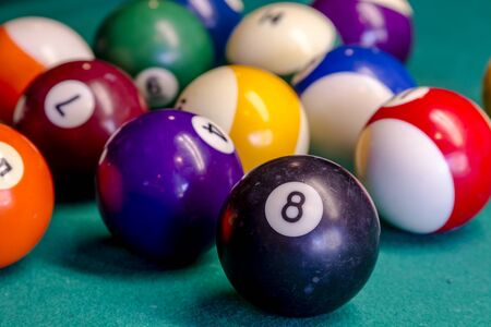 pool hall: Close up of billiard balls sitting on pool table with eight ball in front Stock Photo