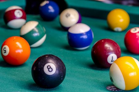 solids: Colorful billiard balls sitting on pool table with eight ball in front Stock Photo