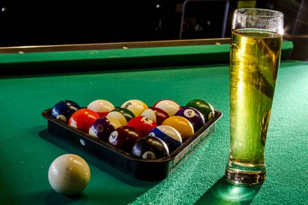 Colorful billiard balls in triangle rack with cue ball sitting on pool table with glass of beer photo