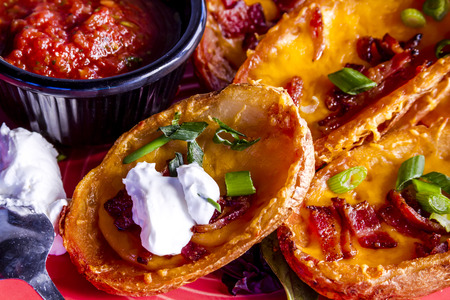 twice: Close up of loaded potato skins appetizer filled with melted cheddar cheese, bacon and onion chives topped with sour cream and spoon Stock Photo