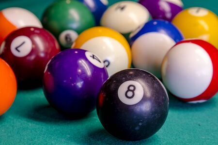 eight ball: Close up of billiard balls sitting on pool table with eight ball in front Stock Photo