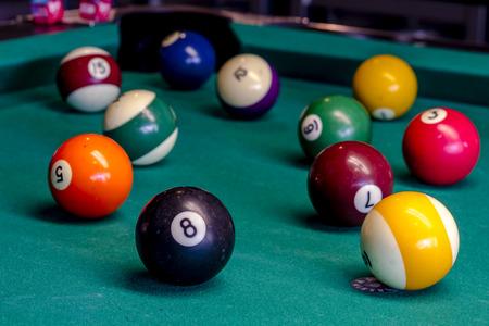bola ocho: Bolas de colores sentados en mesa de billar con la bola ocho en frente Foto de archivo