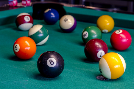 eight ball: Colorful billiard balls sitting on pool table with eight ball in front Stock Photo
