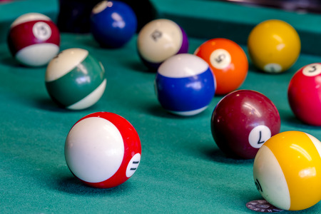 pool hall: Colorful billiard balls sitting on pool table with eight ball in front Stock Photo
