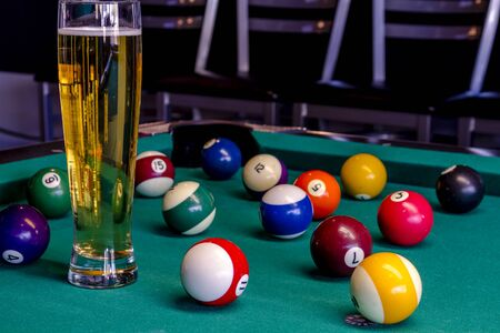 Colorful billiard balls sitting on pool table with glass of beer photo