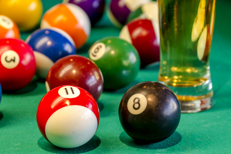 billiards hall: Close up of colorful billiard balls with black eight ball in front sitting on pool table with glass of beer Stock Photo