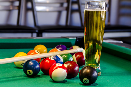 Colorful billiard balls and pool stick sitting on pool table with glass of beer photo