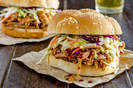 pulled: Two pulled pork barbeque sandwiches with coleslaw sitting on wooden table with glass of beer